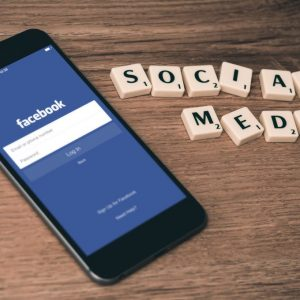 """Photo of cellphone on Facebook with Scrabble tiles spelling out """"Social Media"""""""