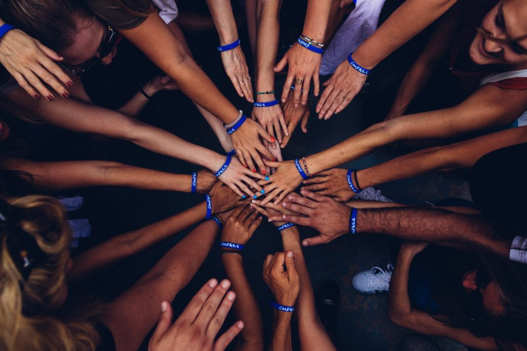 Photo of a group of people wearing RFID bracelets with their hands together in the center of a circle