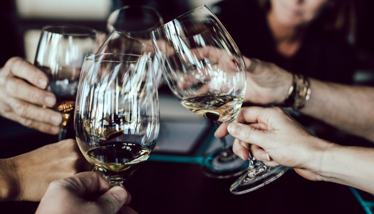 Photo of people clinking wine glasses