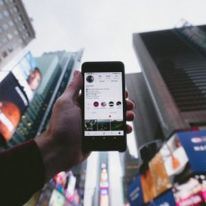 Photo of person holding up a cellphone toward a city skyline